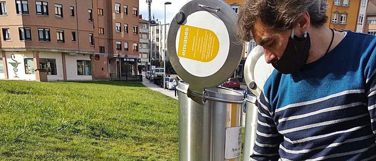 Urce Fernández, vecino, observa uno de los agujeros de los que salen las ratas. En el círculo, uno de los roedores, que apareció muerto en la Avenida de Oviedo. | A. I.