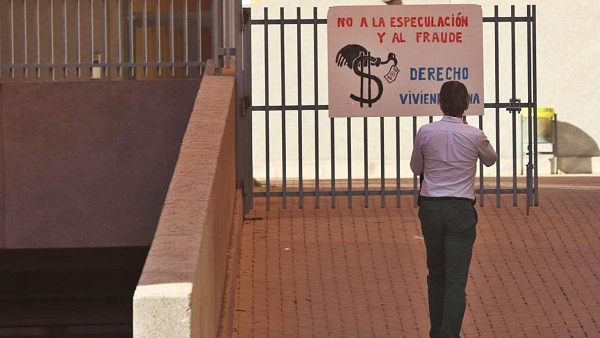 Una persona observa un cartel protesta de los vecinos, el año pasado, a la entrada de un bloque de viviendas. | MEDITERRÁNEO