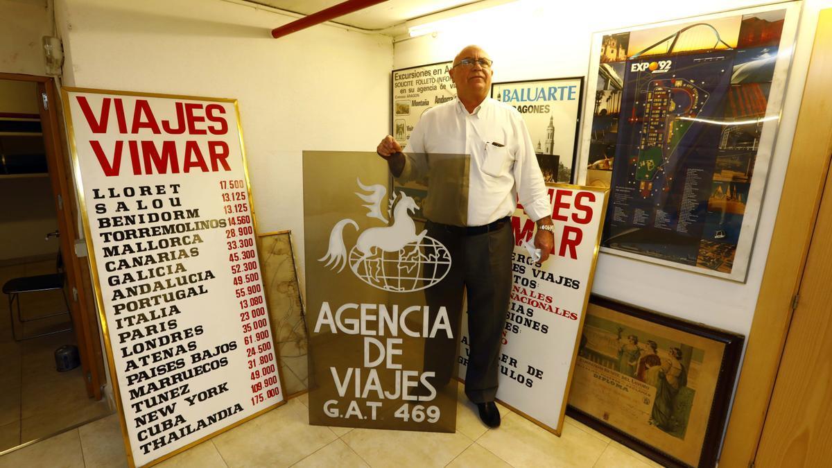 Vicente Martínez, junto a varios carteles publicitarios, con los precios en pesetas, de pasadas campañas.