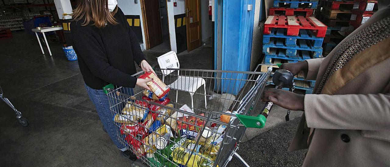 Momento de la entrega de un carro de alimentos a una mujer,  ayer. |  TORTAJADA