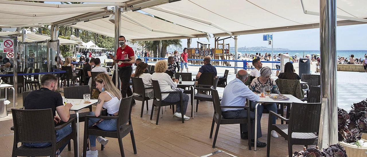 Un camarero sirve en una terrazas llena de gente, este fin de semana en Alicante.   ALEX DOMÍNGUEZ