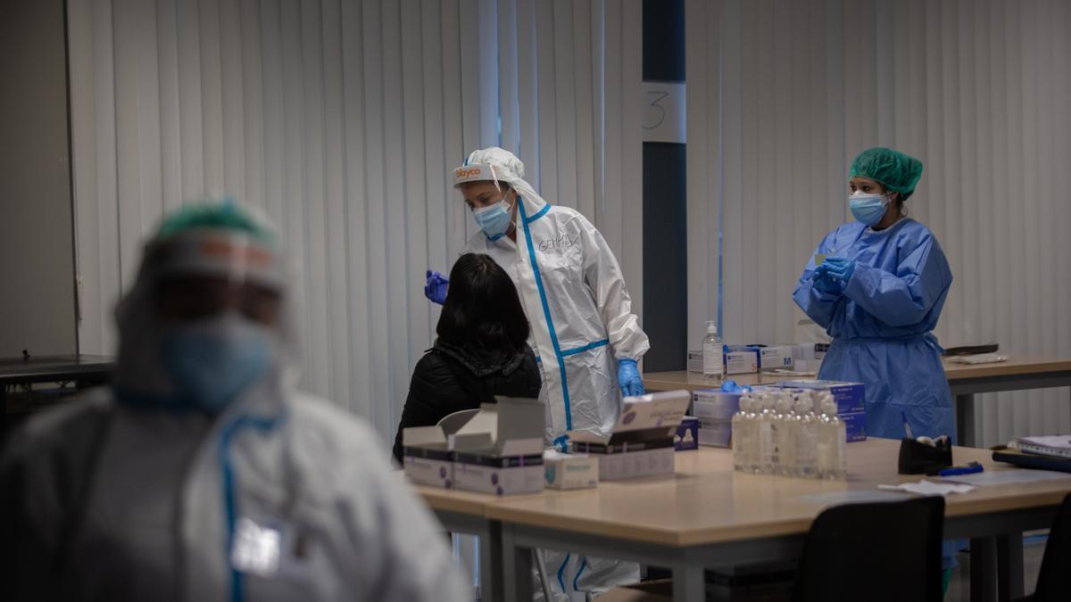 Una mujer recibe una prueba PCR en un dispositivo de cribados masivos.