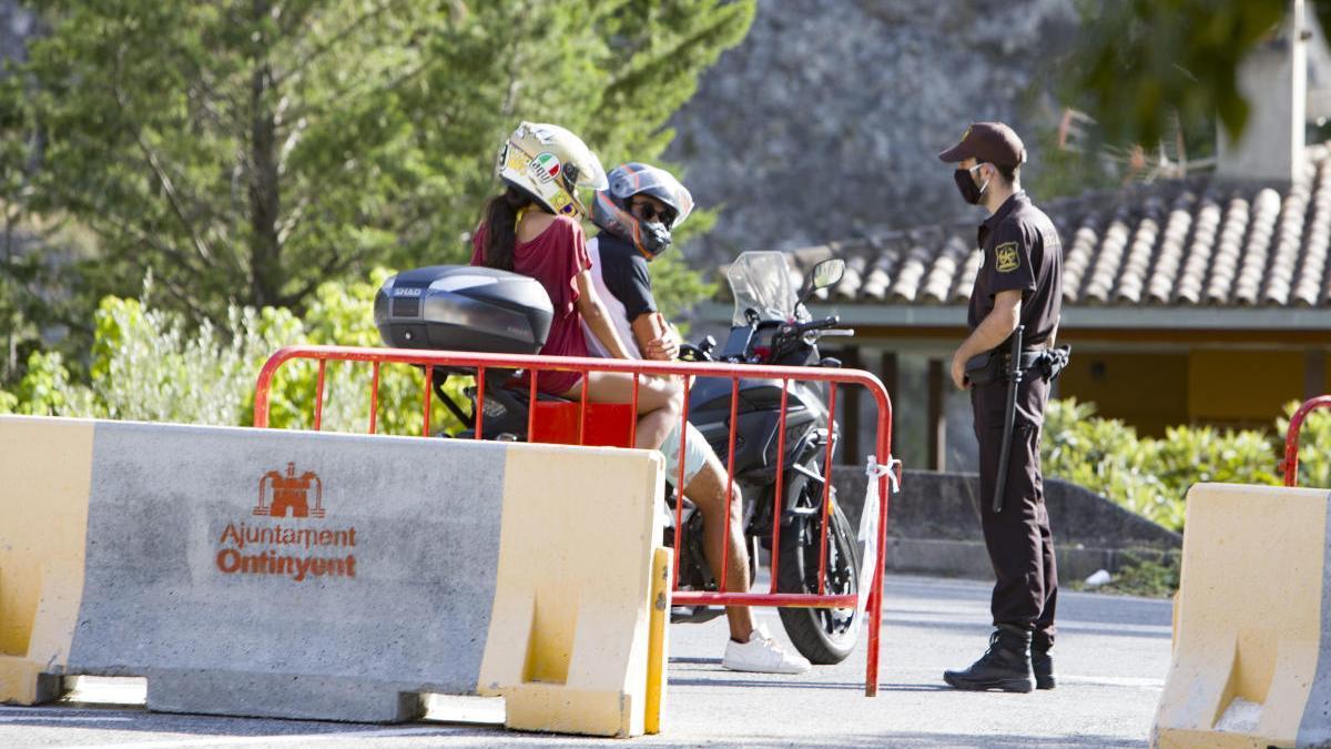 Un vigilante informa a dos visitantes al Pou Clar del cierre del paraje, ayer por la tarde