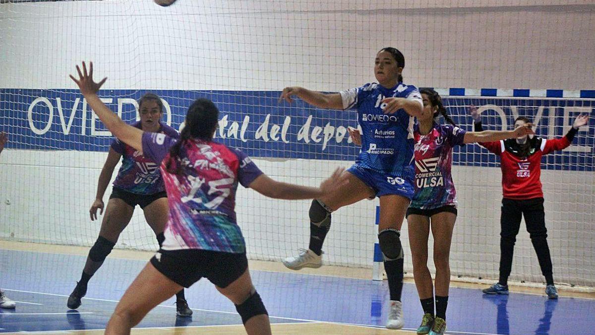 Marta Fernández da un pase entre tres jugadoras del Hand Vall Valladolid.