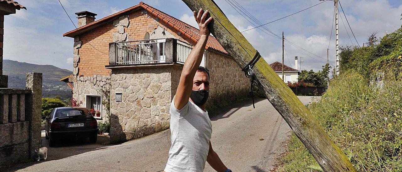 Eloy Diz, vecino de Guillarei, sujetando el poste caído en el tendido eléctrico.