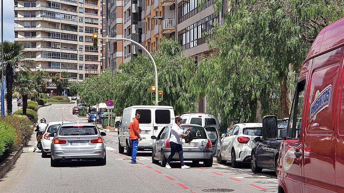 Turismos y vehículos de reparto taponan el ciclocarril que discurre por la calle Travesía.