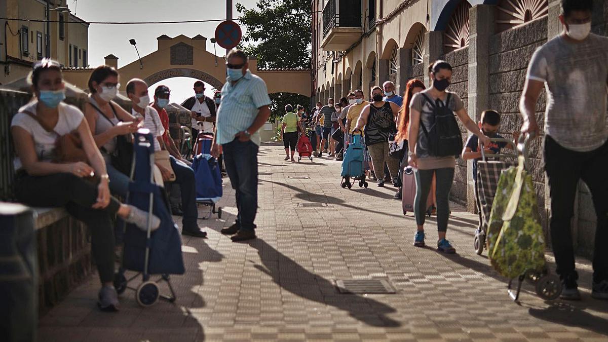 Vecinos hacen cola en el barrio de García Escámez para recoger alimentos.