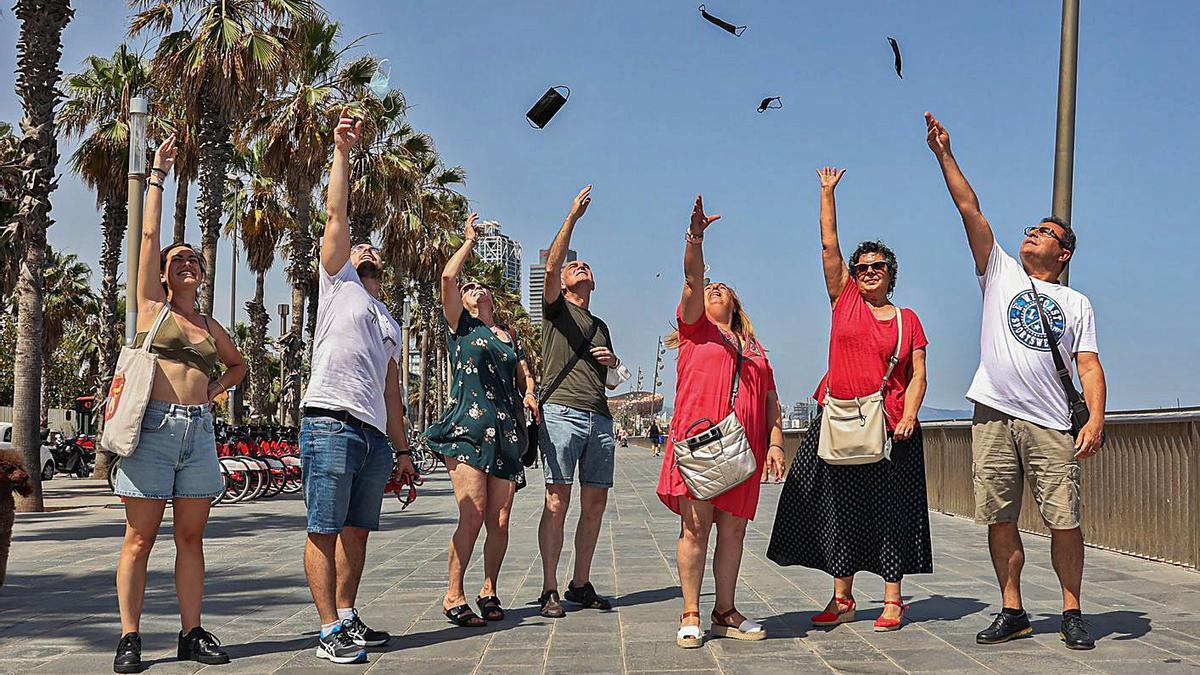 Un grup de gent llença les seves mascaretes a l'aire. | JORDI OTIX