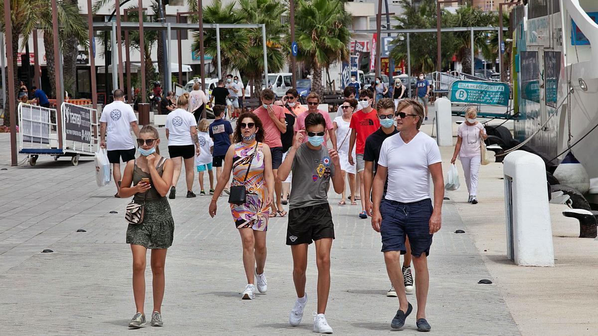 Turistas con y sin mascarilla paseando el pasado martes por el puerto de Vila.   VICENT MARÍ