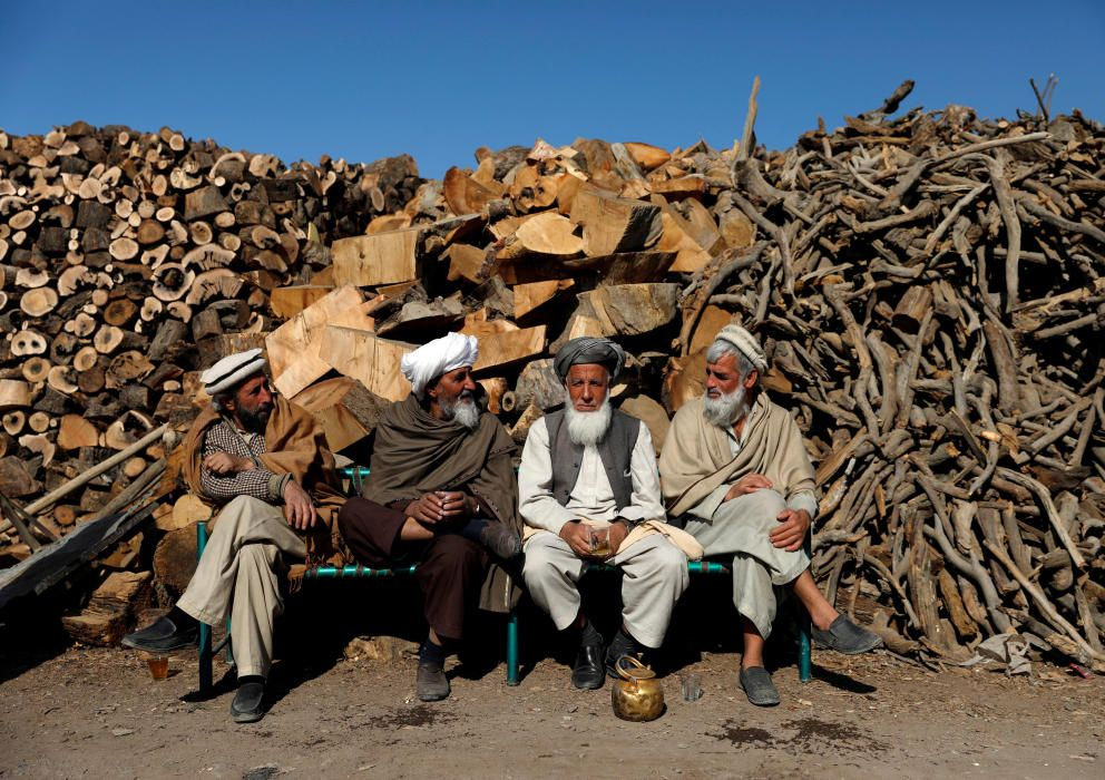 Afghan men sit at their firewood stall in Kabul, ...
