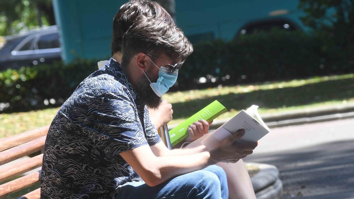 Jóvenes leyendo en un banco de Méndez Núñez durante la pasada edición de la Feria del Libro.