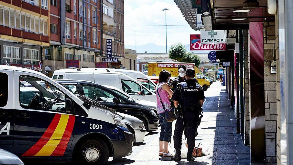 Dos policías explican a una vecina que no puede salir del edificio en cuarentena en Santander.