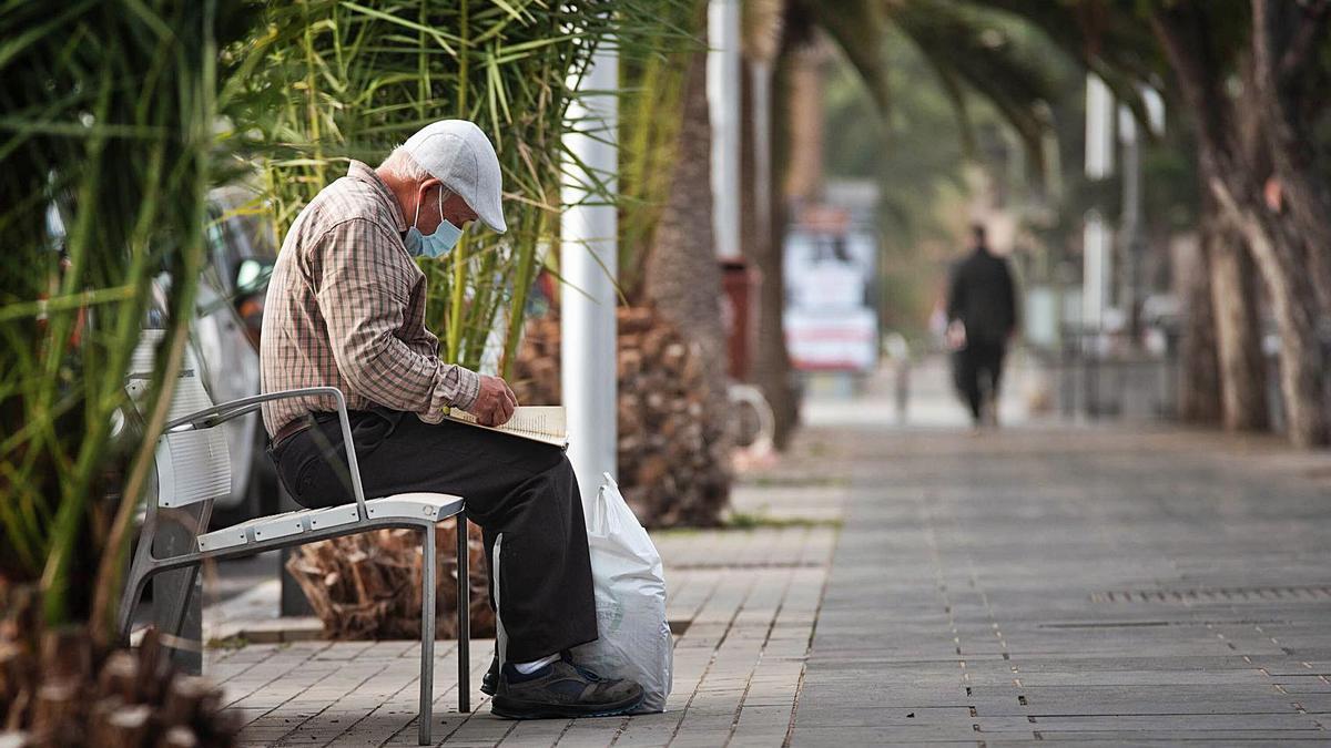 Un señor espera sentado en un banco.