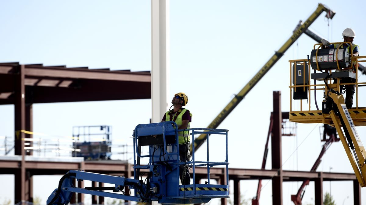 Obreros trabajan con maquinaria de construcción.