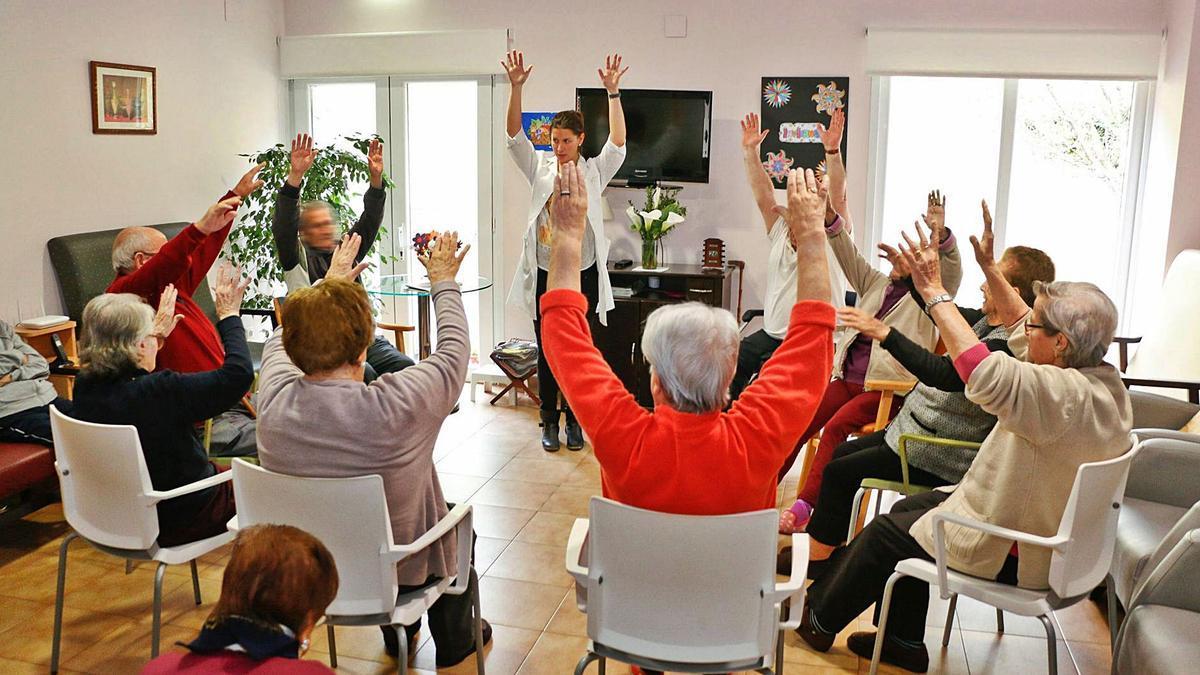 Una profesional realiza ejercicios con un grupo de personas mayores en una residencia.