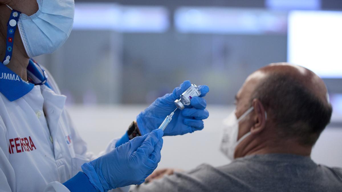 Un sanitario inyecta una vacuna.