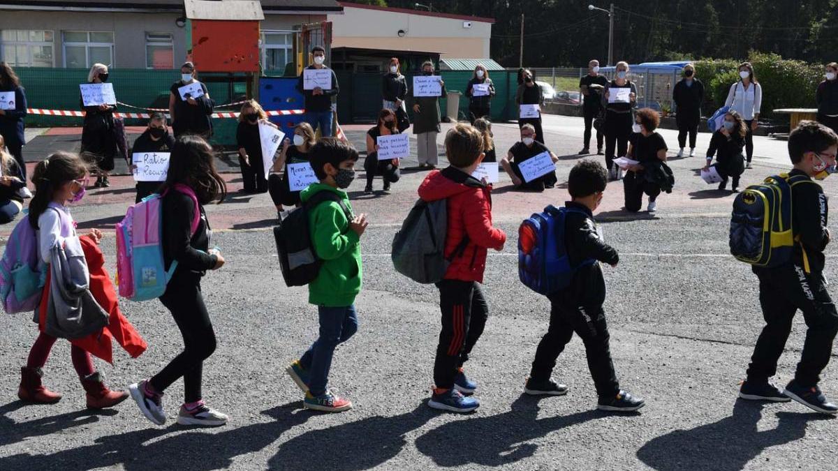 Alumnos de un colegio de A Coruña pasan delante de la protesta de unos padres por los escasos medios para frenar el Covid-19. // V. Echave