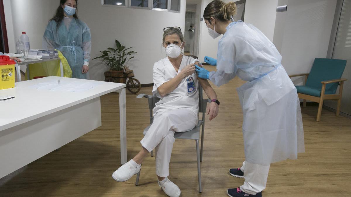 Una técnico auxiliar de cuidados recibe la segunda dosis de la vacuna Pfizer