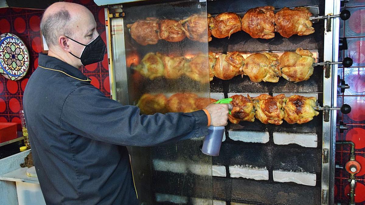 L'encarregat d'El poll bo empolvora amb barreja els pollastres a l'ast | GUILLEM CAMPS