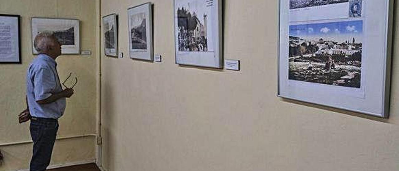 Una persona observa una de las postales expuestas en la Casa de la Cultura de Arucas.