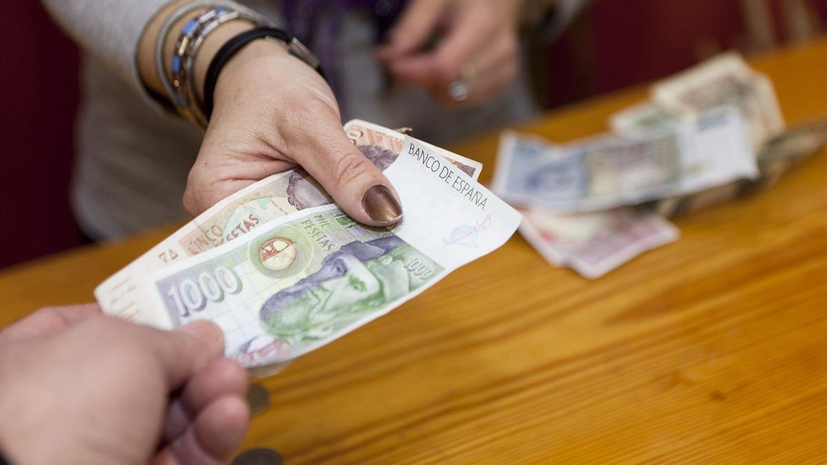 Un hombre paga con las antiguas pesetas.
