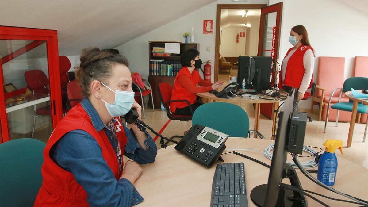 Tres voluntarias, en la sede de Cruz Roja Ourense, llamando por teléfono a personas mayores y jóvenes.