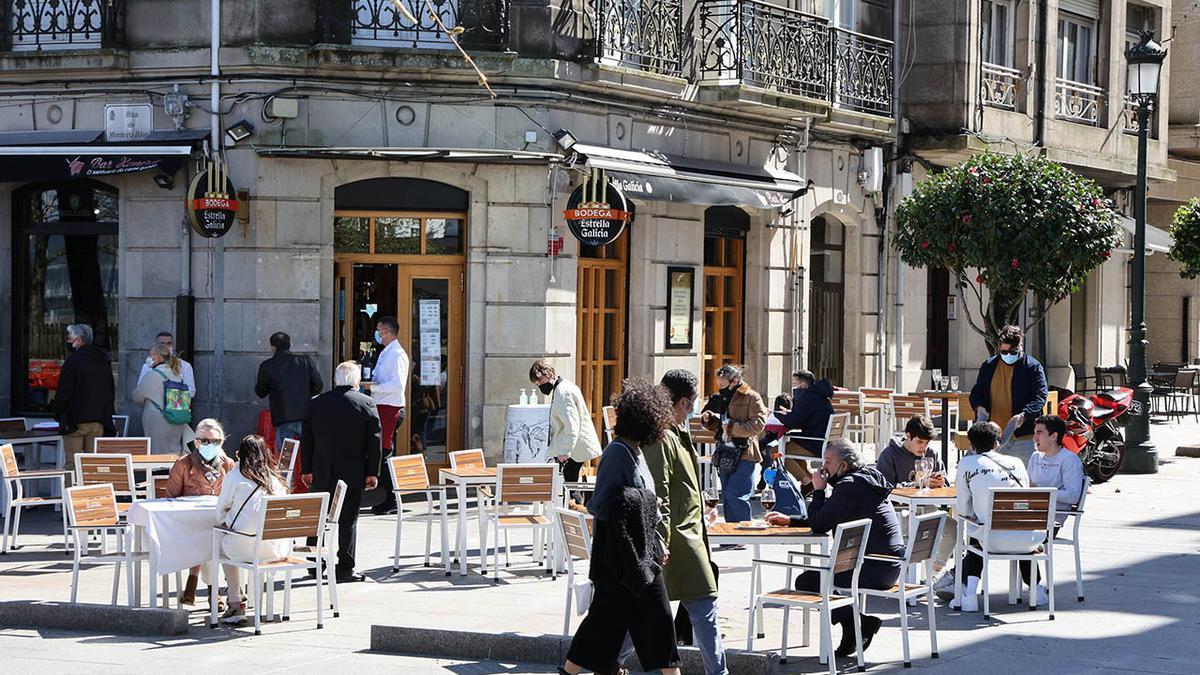Gente paseando y en las terrazas de Praza Compostela de Vigo el pasado puente de San José