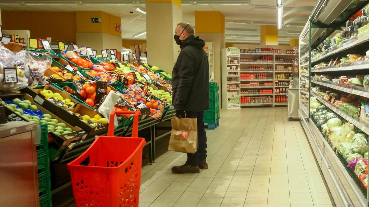 Un hombre en la sección de frutería de un supermercado.