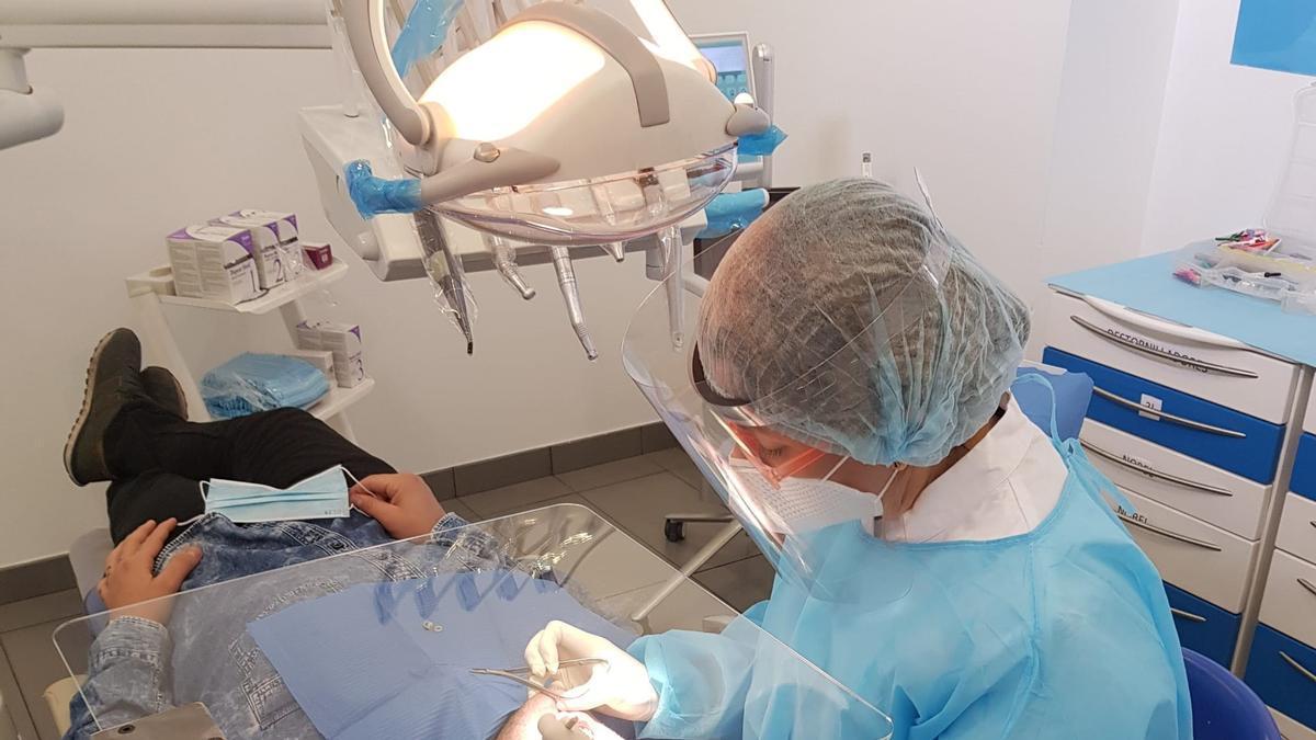 Una odontóloga atiende a un paciente.
