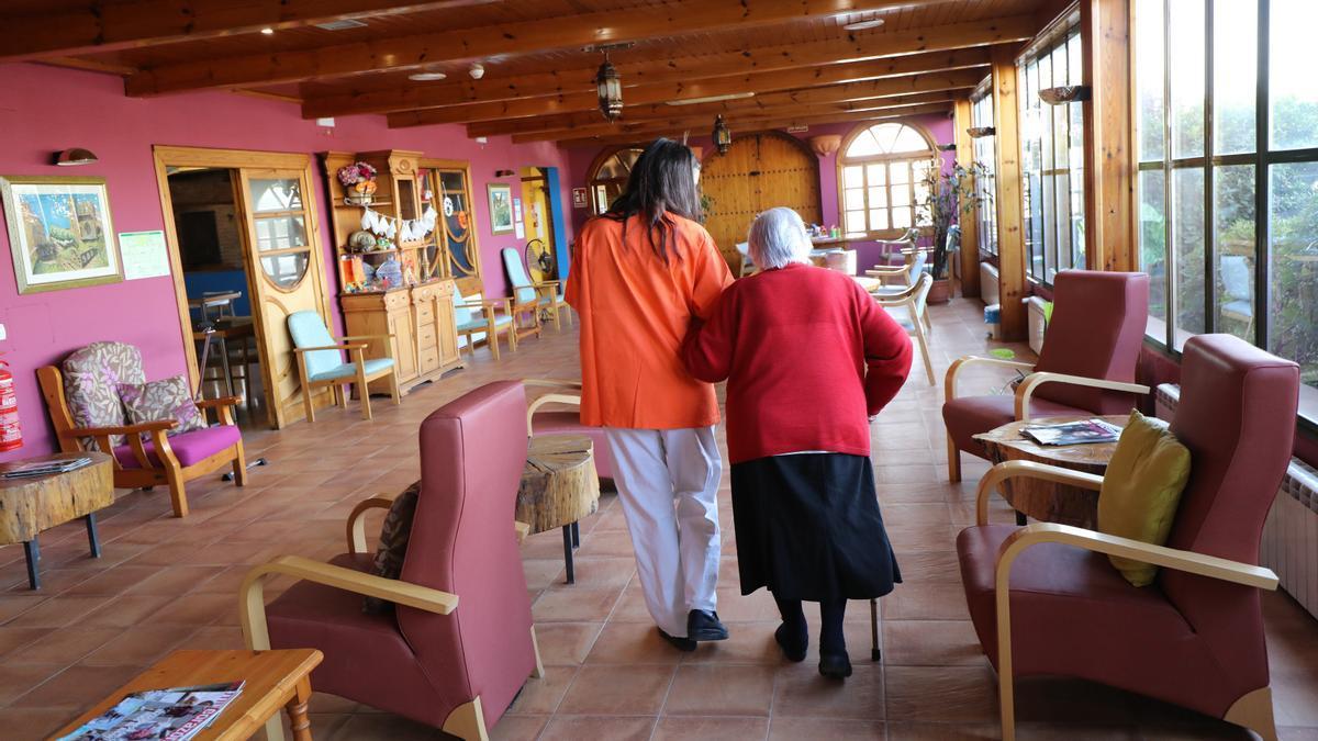 La trabajadora de la residencia La Abubilla, en Huesca, camina con una usuaria del centro
