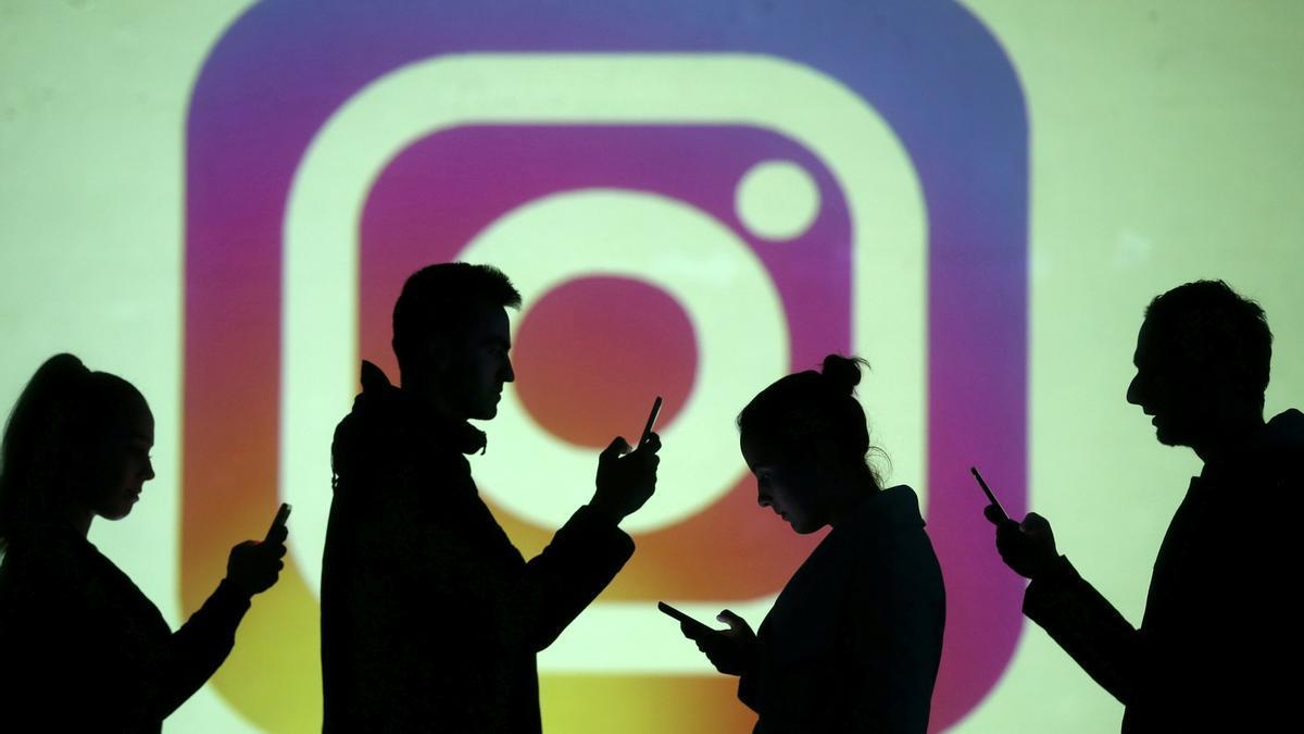 Siluetas frente a un logo de Instagram.