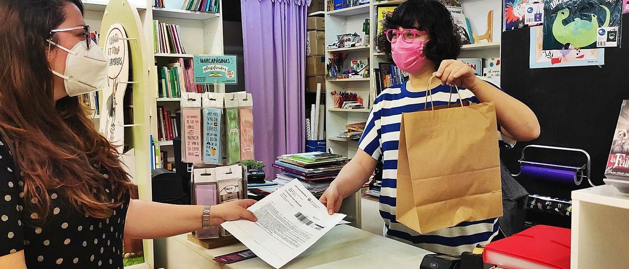 Una clienta paga con cheques en la librería  Gavina Llibres, ayer en Gandia.  j.c. | J.C.