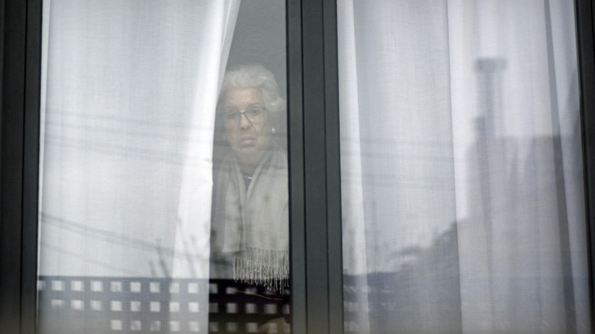 Una anciana mira la calle desde su habitación en una residencia en la Región.