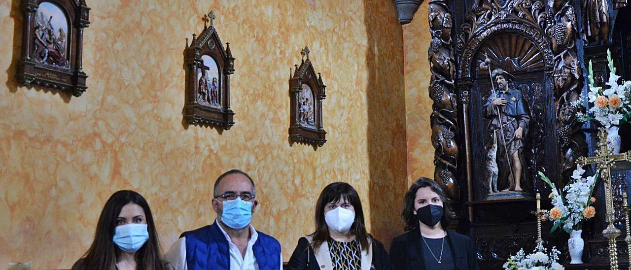Por la izquierda, Raquel Núñez, Victorio Fernández, Amelia Fernández y Ángela Fernández, ante tres piezas del Vía Crucis restaurado colocadas en una de las paredes de la iglesia.  | B. G.