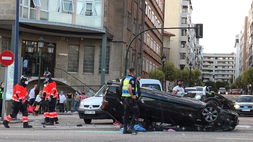 Un coche volcado y desperfectos en una farola y un semáforo tras una colisión en Gran Vía