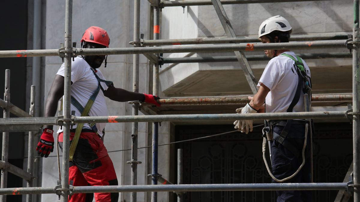 Obreros trabajando en un andamio en verano.