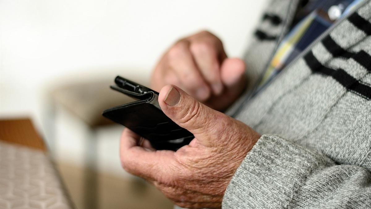 Una persona mayor con un teléfono en la mano