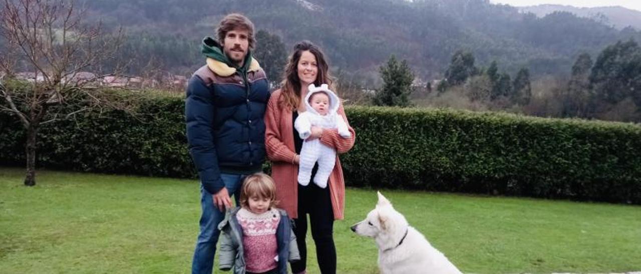"""Alberto García y Almudena Álvarez con Ares y Alma, en brazos, en la terraza de su casa, con su perro """"Yuna""""."""