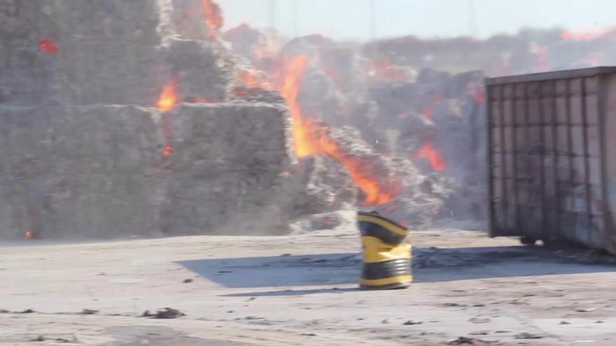 Toneladas de cartón prensado en llamas al arder un almacén de Silla