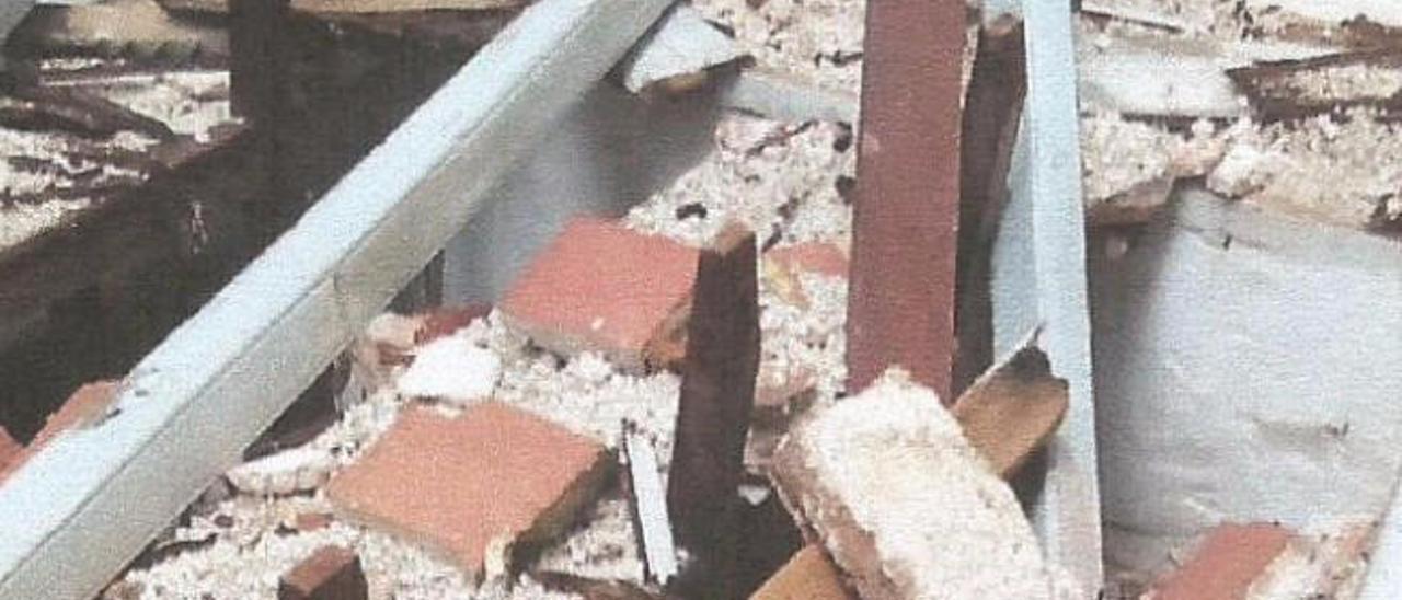 Techo caído sobre los bancos de la ermita.