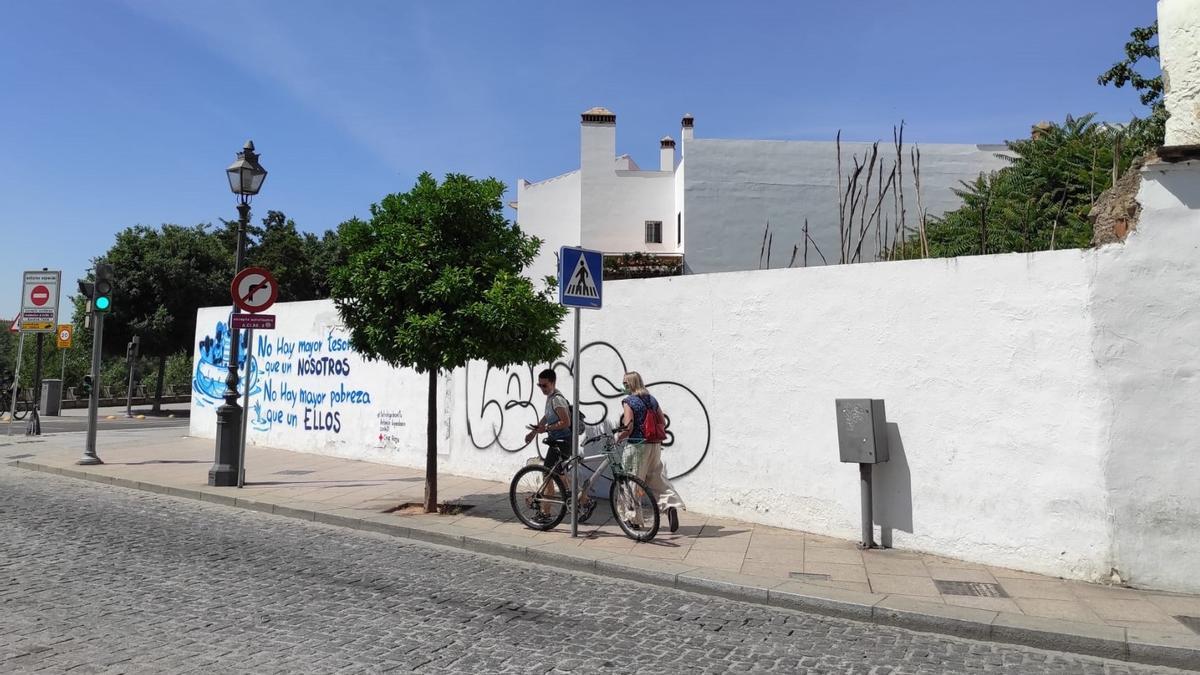 Dos turistas pasan junto al muro que delimita la parcela donde se proyecta el centro de ocio de la Cruz del Rastro.