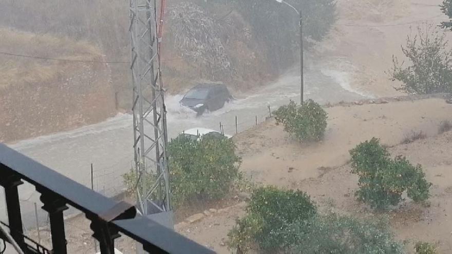 Momento en el que la corriente arrastra un coche en Picassent por el temporal