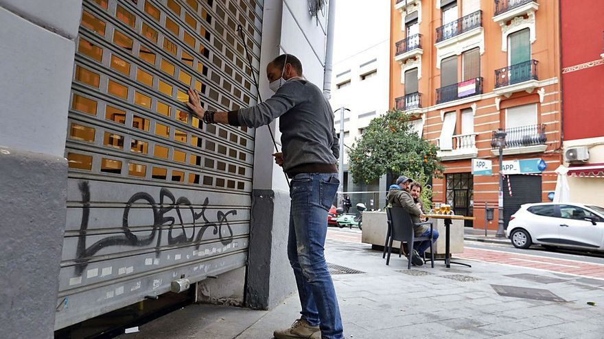 Un trabajador de un bar de Russafa baja la persiana el miércoles, último día de actividad. | M A MONTESINOS