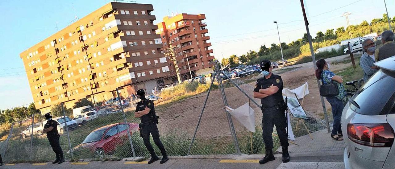 Agentes de la policía vigilan el vallado de los solares y huertos en Benimaclet.   LEVANTE-EMV