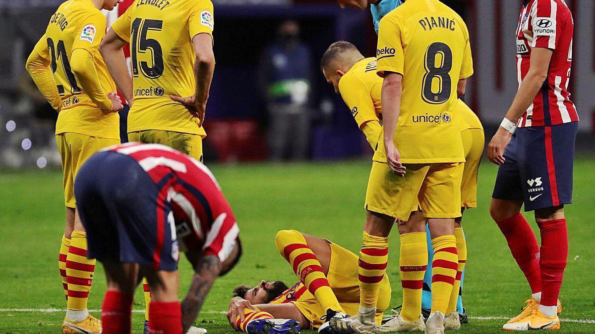 Piqué, en el suelo, se agarra a su rodilla derecha rodeado de compañeros y de rivales.