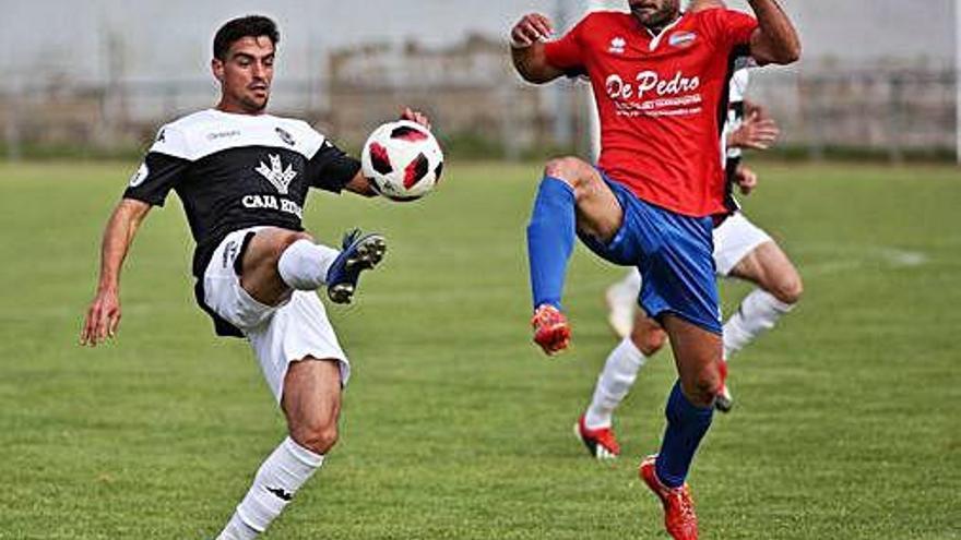 Álvarez toca el balón ante una peligrosa entrada de un jugador del Sporting Uxama.