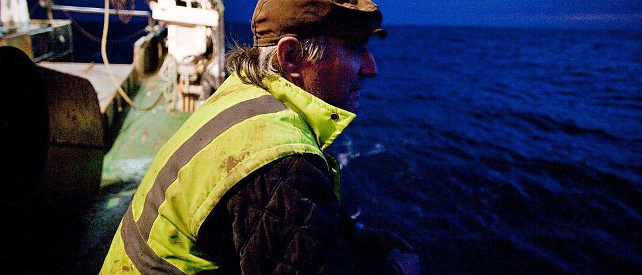 Un pescador observa amanecer en alta mar desde un arrastrero en una pasada costera de la xarda.