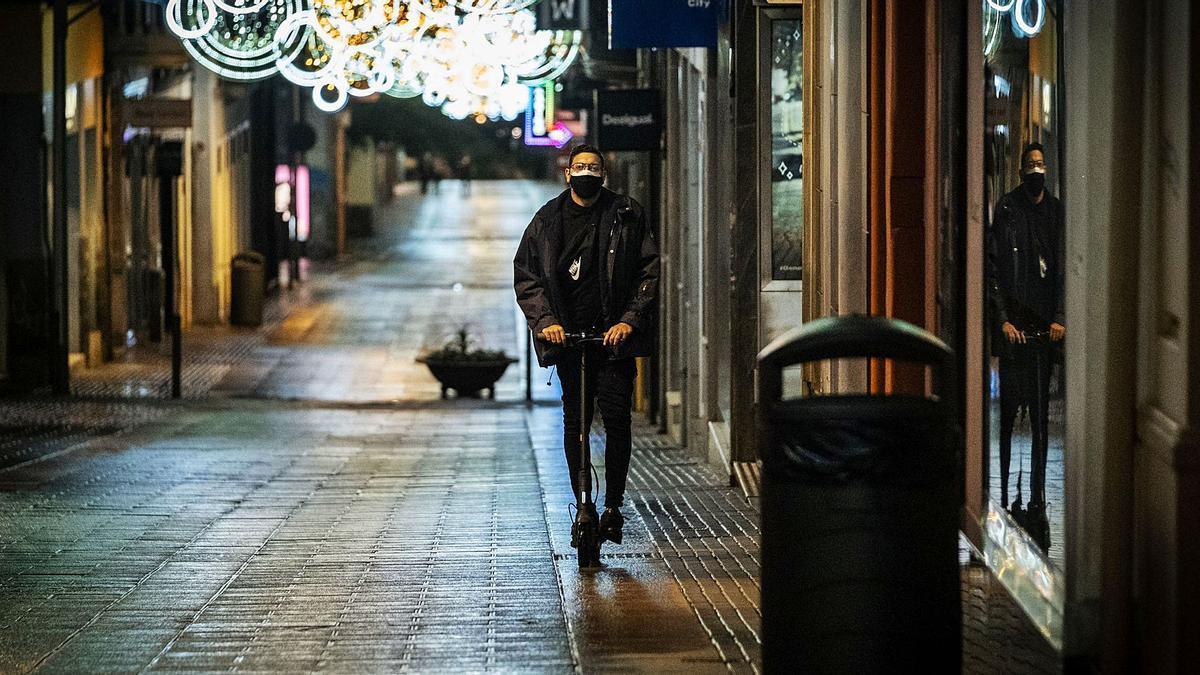 Un ciudadano sube la calle Castillo de la capital tinerfeña con un patinete eléctrico al inicio de la madrugada de ayer.