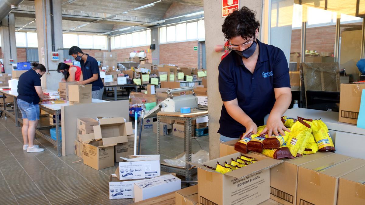 Usuaris del centre ocupacional de la Fundació Els Joncs preparant els lots de menjar