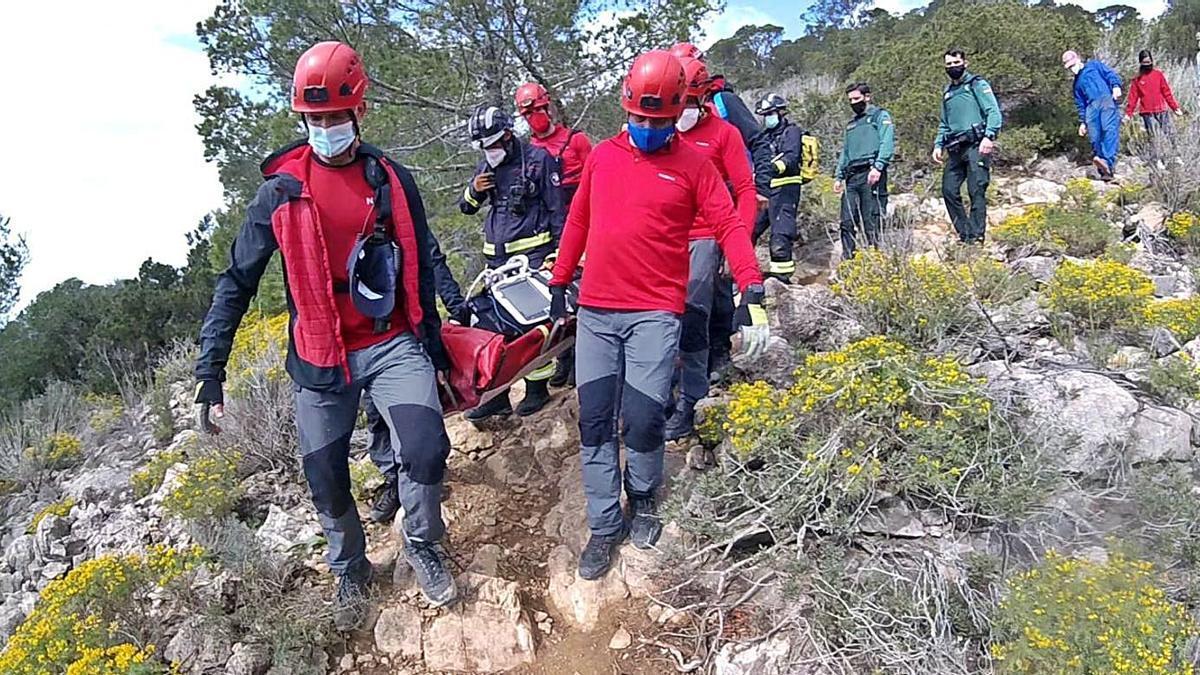 Dos imágenes de los bomberos llevando en camilla al herido desde la cima de es Cap Nunó hasta donde se encontraba la ambulancia, a unos 400 metros.